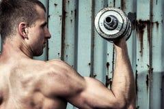 Chiuda sul giovane uomo atletico che fa l'allenamento con la testa di legno pesante Immagini Stock