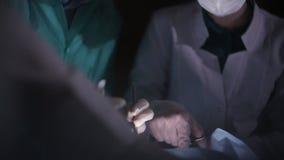 Chiuda sul gruppo chirurgico delle mani che assiste il funzionamento del chirurgo sul paziente nel teatro dell'ospedale archivi video