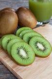 Chiuda sul kiwi e sul succo affettati del kiwi sul booard di legno Immagini Stock Libere da Diritti