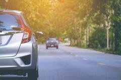 Chiuda sul lato posteriore di nuovo parcheggio d'argento dell'automobile della berlina sulla strada asfaltata Immagine Stock