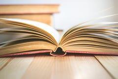 Chiuda sul libro aperto e sulla pila di libri con lo spazio della copia nell'umore di rilassamento Fotografia Stock Libera da Diritti