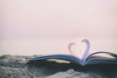 Chiuda sul libro del cuore sulla sabbia nella spiaggia con il fondo d'annata della sfuocatura del filtro Immagine Stock Libera da Diritti