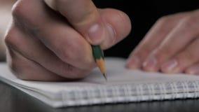 Chiuda sul macro colpo eccellente di una scrittura della mano dell'uomo qualcosa sulla matita di carta del taccuino video d archivio
