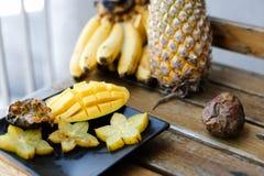 Chiuda sul mango squisito con la carambola sul piatto vicino all'ananas ed alle banane sulla tavola di legno fotografia stock libera da diritti