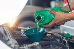 Chiuda sul meccanico della mano che ripara il cambiamento l'olio Meccanico di automobile po immagini stock