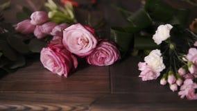Chiuda sul metraggio dei fiori, dei nastri e di altri strumenti del fiorista professionista trovantesi sulla tavola Disposizione  stock footage