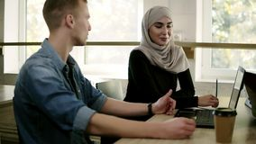 Chiuda sul metraggio della gente di affari multirazziale che si incontra nell'ufficio luminoso moderno alla tavola di legno Giova video d archivio
