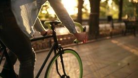 Chiuda sul metraggio di un uomo che cicla un parco o un boulevard della bicicletta di mattina Vista laterale di un giovane che gu stock footage