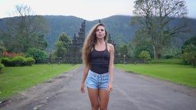 Chiuda sul modello grazioso nella cima nera ed i jeans mettono camminano lungo la strada in mezzo della giungla video d archivio