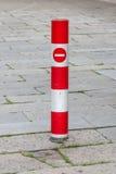 Chiuda sul palo rosso di traffico e su nessun segno dell'entrata con la passeggiata del mattone Fotografie Stock