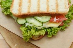 Chiuda sul panino succoso con bacon, gli ortaggi freschi, l'insalata verde e le linee scure dopo la griglia fotografia stock libera da diritti