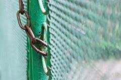 Chiuda sul portone verde del recinto fissato catena Immagine Stock
