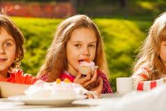 Chiuda sul punto di vista dei bambini che bevono il tè con i bigné immagini stock libere da diritti