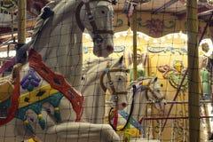Chiuda sul punto di vista dei cavalli di un carosello Fotografie Stock