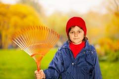 Chiuda sul punto di vista del ragazzo che tiene il rastrello rosso in parco Immagini Stock