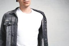 Chiuda sul punto di vista del tipo sorridente in maglietta e rivestimento bianchi fotografie stock libere da diritti