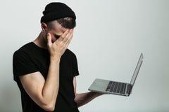 Chiuda sul punto di vista dell'uomo con il computer portatile e il facepalm immagini stock