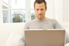 Chiuda sul punto di vista dell'uomo professionale con il computer portatile ed il telefono astuto a casa. Fotografia Stock Libera da Diritti