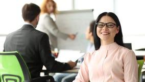 Chiuda sul punto di vista della donna di affari castana attraente che si siede nella sala riunioni stock footage
