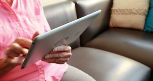 Chiuda sul punto di vista della donna pensionata che gioca con il computer della compressa archivi video