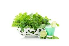 Chiuda sul punto di vista delle verdure verdi in ciotola e cocktail bianchi Immagini Stock