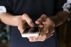 Chiuda sul punto di vista di un uomo che tiene uno Smart Phone Vestiti casuali Fotografia Stock Libera da Diritti