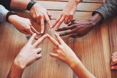 Chiuda sul punto di vista superiore dei giovani che un le loro mani Gli amici che fanno una stella modellano con le dita che most immagine stock