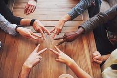 Chiuda sul punto di vista superiore dei giovani che un le loro mani Gli amici che fanno una stella modellano con le dita che most fotografia stock