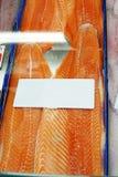 Chiuda sul raccordo di color salmone su ghiaccio con l'etichetta bianca dell'etichetta al marke del pesce Fotografia Stock