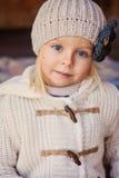 Chiuda sul ritratto all'aperto della ragazza sorridente adorabile del bambino in cappello e cappotto tricottati beige Immagine Stock