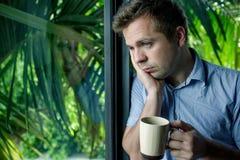 Chiuda sul ritratto del caffè bevente dell'uomo d'affari uomo che guarda la finestra della depressione e che tiene tazza immagini stock