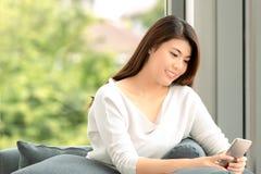 Chiuda sul ritratto del colpo di giovane bella donna asiatica che si siede sopra immagine stock