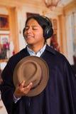 Chiuda sul ritratto del giovane indigeno latino bello con le cuffie Fotografie Stock Libere da Diritti