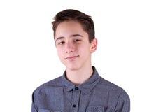 Chiuda sul ritratto dell'adolescente sveglio sorridente dei giovani in camicia grigia, isolato su fondo bianco Fotografia Stock