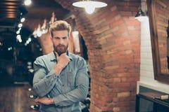 Chiuda sul ritratto dell'uomo barbuto rosso alla moda duro in un barbiere s immagini stock