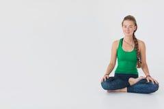 Chiuda sul ritratto della donna attraente che si siede nel meditare la posizione sul pavimento bianco Ragazza che solleva le mani Fotografia Stock Libera da Diritti