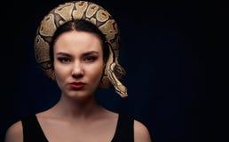 Chiuda sul ritratto della donna con il serpente intorno alla sua testa sulle sedere scure fotografie stock