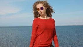 Chiuda sul ritratto della donna in mano corrente degli occhiali da sole d'avanguardia di modo tramite capelli ricci che soffiano  stock footage