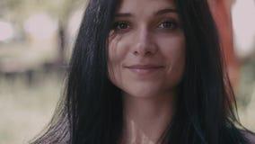 Chiuda sul ritratto della giovane donna castana esaminando la macchina fotografica e sorridendo sul fondo vago all'aperto stock footage