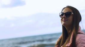Chiuda sul ritratto della giovane donna che sorride con i capelli marroni che soffiano in vento che guarda il arround archivi video