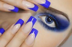 Chiuda sul ritratto della giovane donna con i grandi occhi azzurri e manicure di prefetto immagine stock