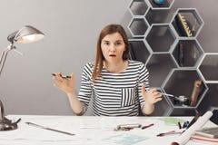 Chiuda sul ritratto della mano di diffusione del bello giovane progettista indipendente femminile europeo divertente nello sguard Immagini Stock