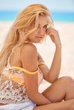 Chiuda sul ritratto della ragazza bionda sulla spiaggia Fotografia Stock