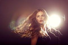 Chiuda sul ritratto della ragazza del modello di moda con capelli di salto lunghi Fotografie Stock