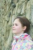 Chiuda sul ritratto della ragazza sorridente in una giacca sportiva colorata con il fondo delle pietre Fotografia Stock