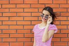 Chiuda sul ritratto della ragazza sveglia che indossa i vetri alla moda rosa che guardano da parte sopra il fondo rosso del muro  fotografia stock