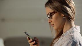 Chiuda sul ritratto della ragazza sveglia con lo smartphone della tenuta dei capelli ricci archivi video