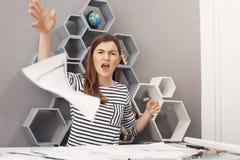 Chiuda sul ritratto delle carte di lavoro di lancio del giovane bello ingegnere indipendente femminile infelice via con arrabbiat fotografie stock