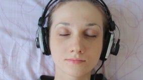 Chiuda sul ritratto delle cuffie d'uso della giovane donna romantica attraente che ascoltano la musica che si rilassa nella camer stock footage