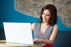 Chiuda sul ritratto di bella giovane donna che esamina il computer portatile Fotografia Stock